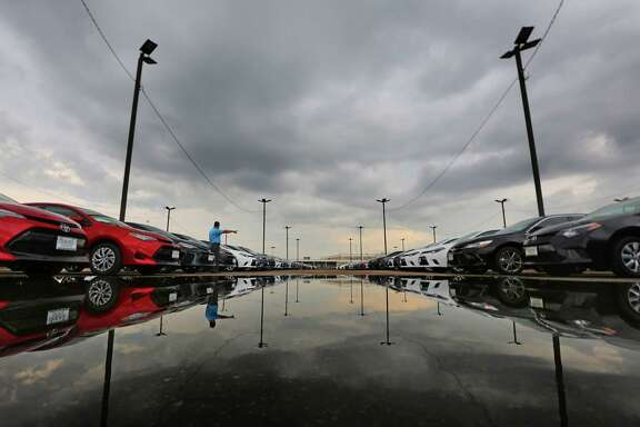 Sales consultant Bhong Zausa points out new Toyotas lined up awaiting sale in the back lot at the Sterling McCall Toyota dealership on the Southwest Freeway, Thursday, Oct. 20, 2016, in Houston. ( Mark Mulligan / Houston Chronicle )