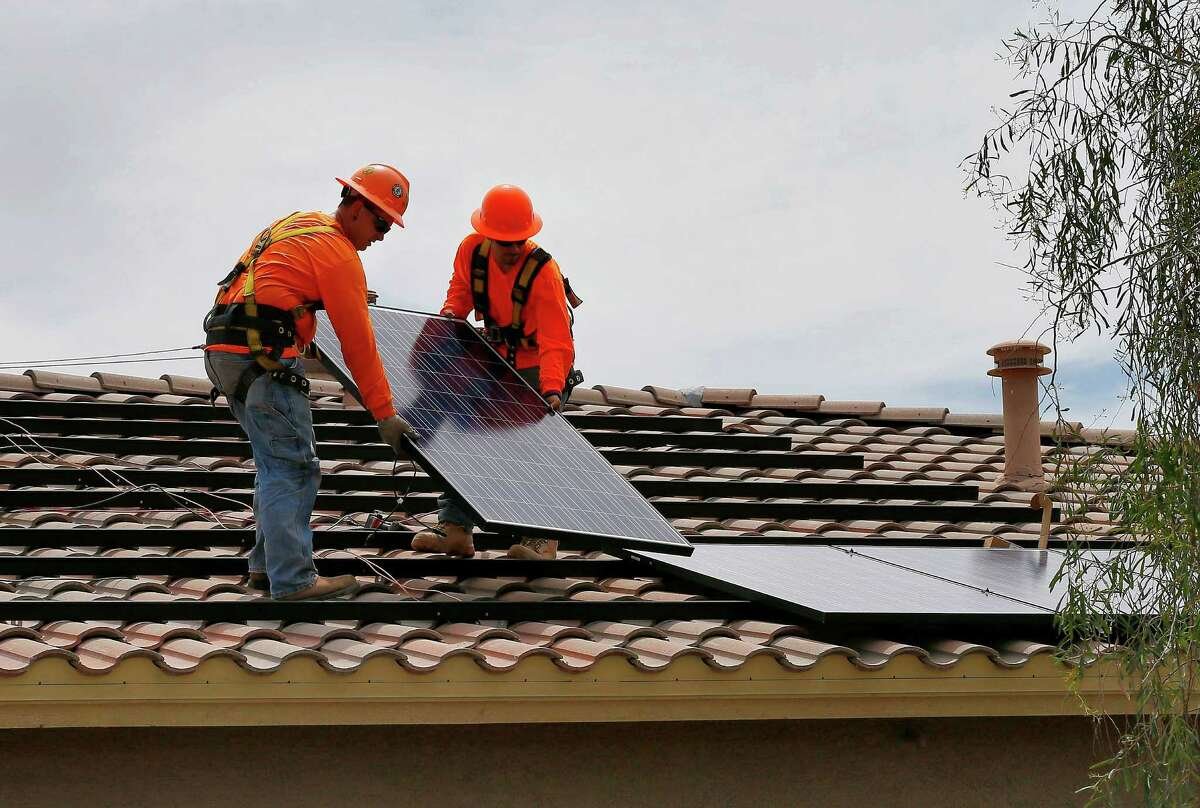 FILE--In this July 28, 2015, file photo, electricians Adam Hall, right, and Steven Gabert, install solar panels on a roof for Arizona Public Service company in Goodyear, Ariz. On Wednesday, June 1, 2016, Arizona's largest electric utility wants to increase residential electricity rates by about 8 percent, move most customers to a billing plan that charges them more if their power use surges during peak hours and wants to end solar power buyback plans it says don't fairly cover the costs of providing power to homes with solar panels starting in mid-2017. (AP Photo/Matt York, file)