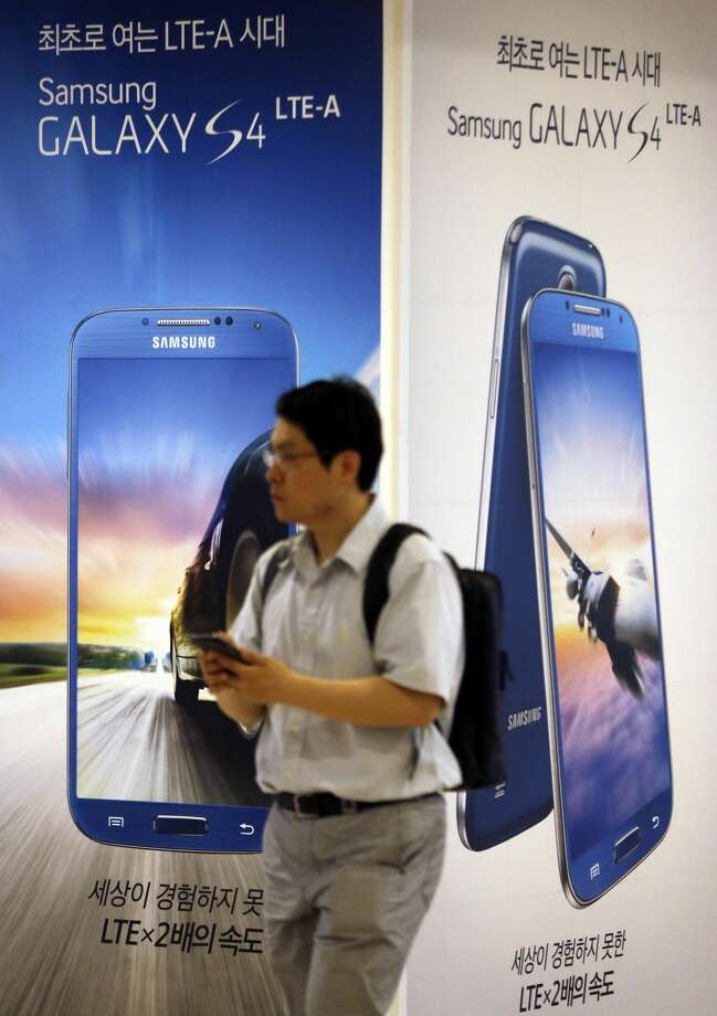 A man walks by the billboards of Samsung Electronics' Galaxy S4 LTE-A smartphone at a showroom of its headquarters in Seoul, South Korea, Friday, July 5, 2013. (AP Photo/Lee Jin-man)