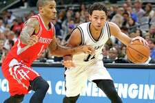 Spurs' Bryn Forbes looks for room around the Houston Rockets' Gary Payton II during second half action of a preseason game on Oct. 21, 2016 at the AT&T Center.