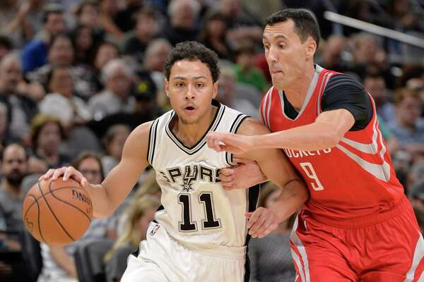 San Antonio Spurs guard Bryn Forbes (11) drives around Houston Rockets guard Pablo Prigioni, of Argentina, during the second half of a preseason NBA basketball game, Friday, Oct. 21, 2016, in San Antonio. (AP Photo/Darren Abate)