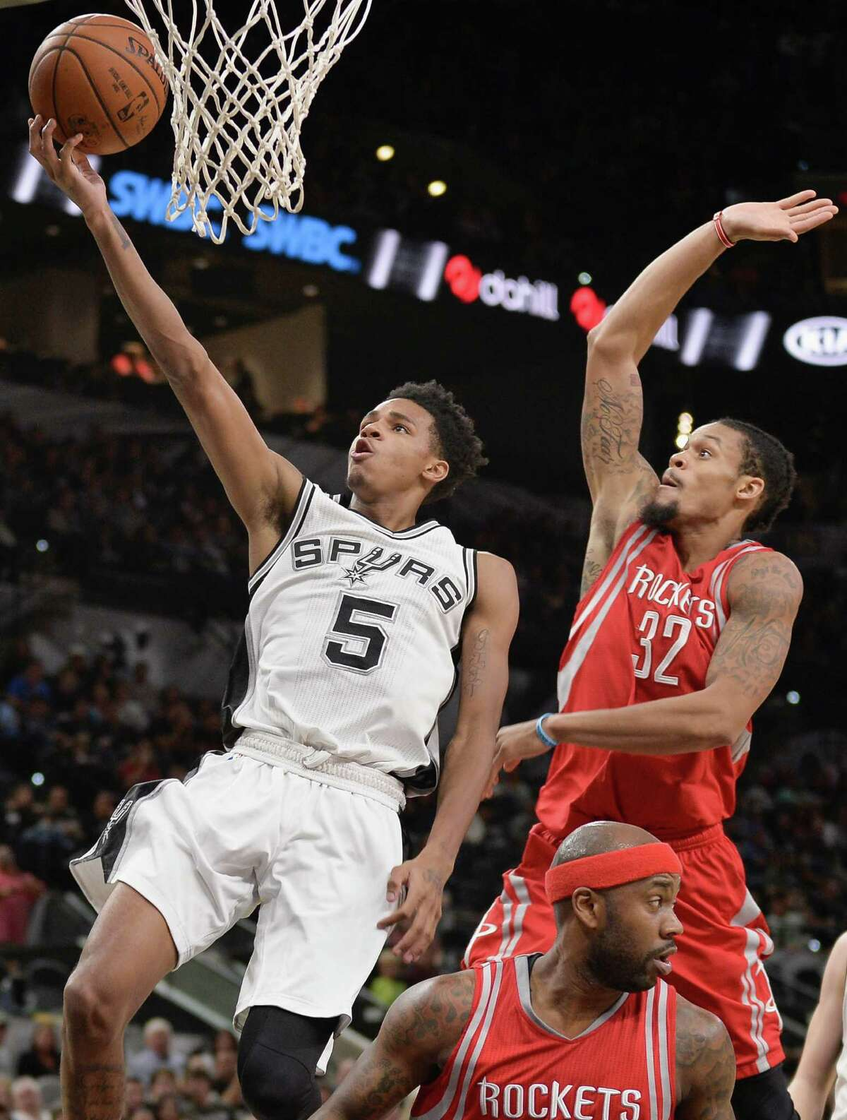 San Antonio Spurs guard Dejounte Murray (5) shoots next to Houston Rockets guard K.J. McDaniels (32) during the second half of a preseason NBA basketball game, Friday, Oct. 21, 2016, in San Antonio. (AP Photo/Darren Abate)