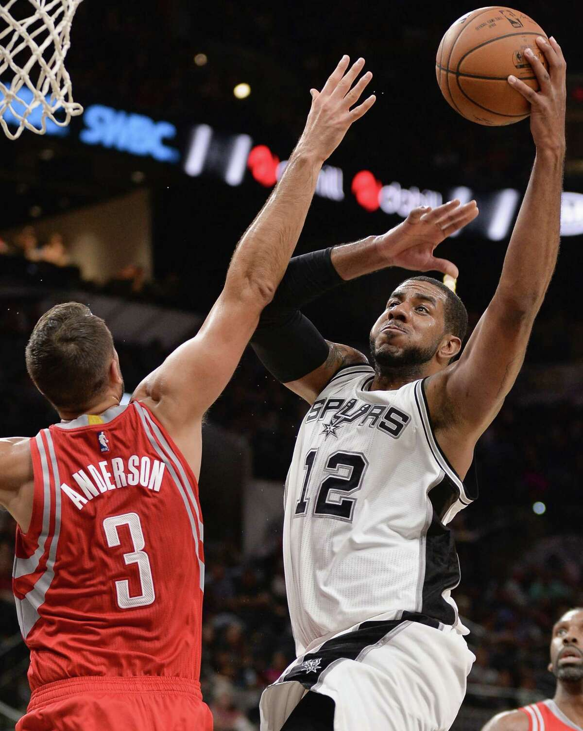 San Antonio Spurs forward LaMarcus Aldridge (12) shoots against Houston Rockets forward Ryan Anderson during the second half of a preseason NBA basketball game, Friday, Oct. 21, 2016, in San Antonio. (AP Photo/Darren Abate)