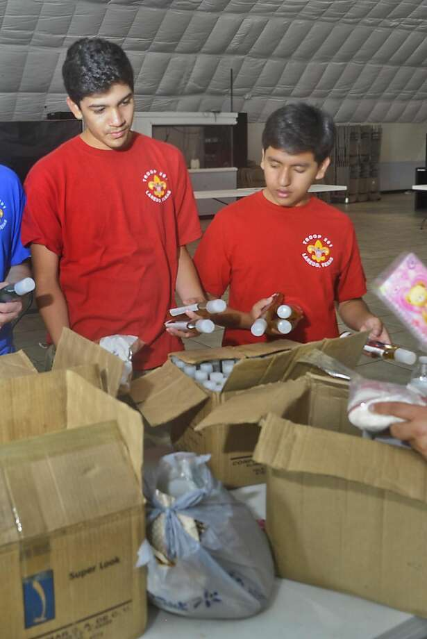 Troop 201's Jorge Carrion and Arturo Fernandez sort through boxes of shampoo on Sunday afternoon at Dunamis Ministries Church as they prepare boxes and bags of basic necessities that will be sent to two orphanages in the Dominican Republic. Photo by Danny Zaragoza