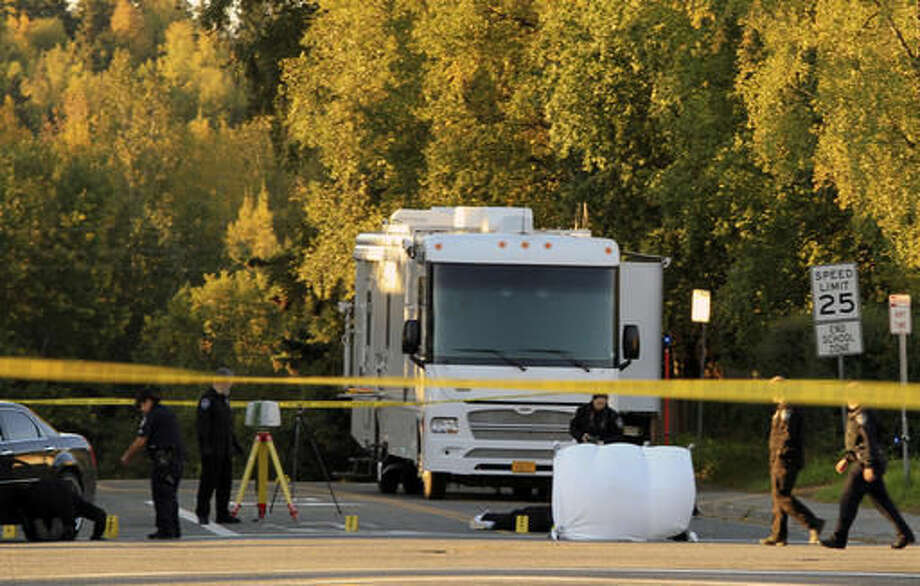 Anchorage police process a crime scene near two downtown schools in which a man was found fatally shot on Tuesday, Sept. 13, 2016, in Anchorage, Alaska. The intersection at 15th Avenue and C Street borders Central Middle School and is two blocks from Chugach Optional Elementary School. The shooting occurred before the schools opened but the schools were closed for the day. (AP Photo/Dan Joling)