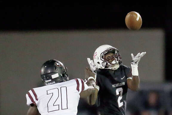 Pearland's Jaelin Benefield (2) makes a catch against George Ranch defender Brent Ugo (21) during the first half of Friday's game at the Rig in Pearland.