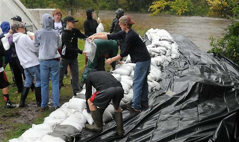 In this Thursday, Sept. 22, 2016 photo, residents lay down sandbags to protect the city's water treatment plant from the rising Le Sueur River, in St. Clair, Minn. (Pat Christman/The Free Press via AP)