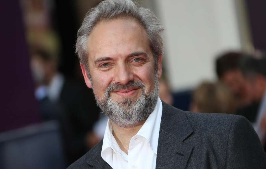 "In this June 25, 2013 file photo, director Sam Mendes arrives for the opening night of the musical ""Charlie and the Chocolate Factory,"" at the Drury Lane Theatre in central London. Mendes is coming back to direct another James Bond film with Daniel Craig following the enormously successful ""Skyfall."" Mendes had suggested ""Skyfall"" would be his lone entry in the 007 canon, but Bond producers and Sony Pictures announced his return Thursday, July 11. (Photo by Joel Ryan/Invision/AP, File)"
