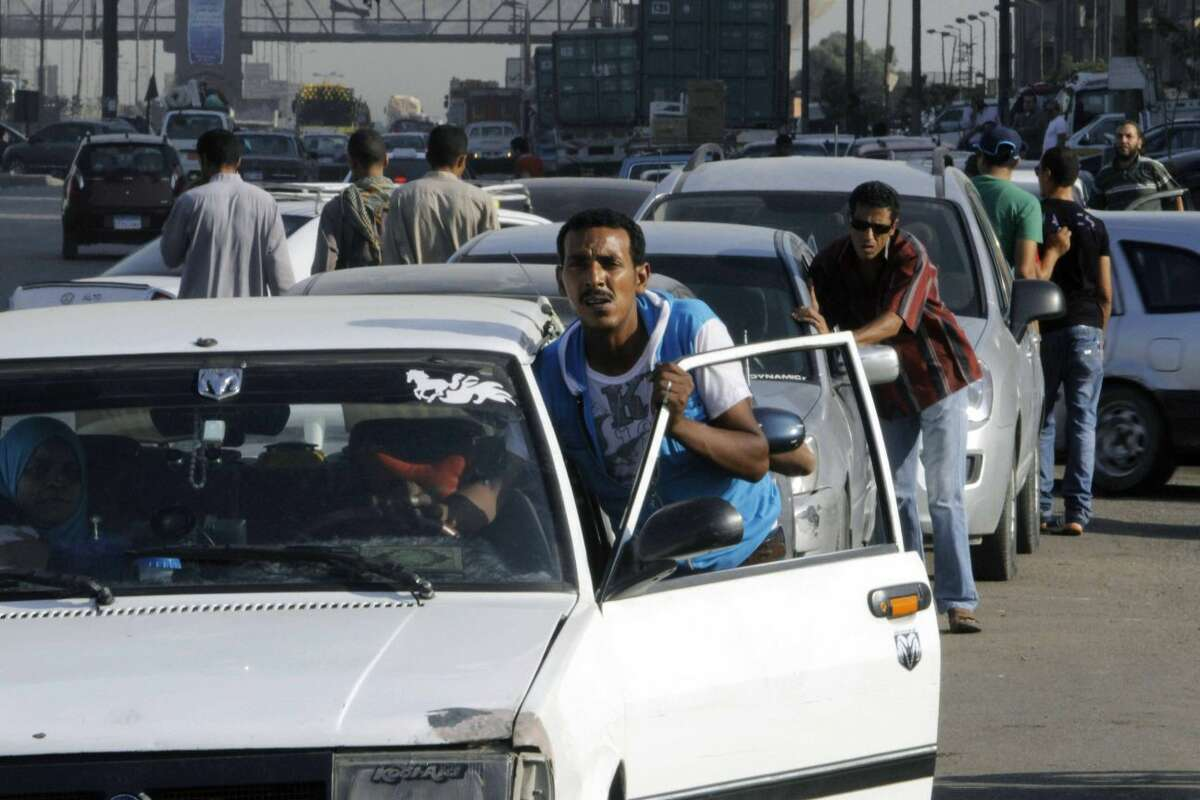In this Tuesday, June 25, 2013 file photo, Egyptian drivers push their cars as they wait in long queues at a gasoline station in Cairo, Egypt. As the streets once again fill with protesters eager to oust the president and Islamists determined to keep him in power, Egyptians are preparing for the worst: days or weeks of urban chaos that could turn a loved one into a victim. Households already beset by power cuts, fuel shortages and rising prices are stocking up on goods in case the demonstrations drag on. Businesses near protest sites are closing until crowds subside. Fences, barricades and walls are going up near homes and key buildings. And local communities are organizing citizen patrols in case security breaks down. (AP Photo/Amr Nabil, File)