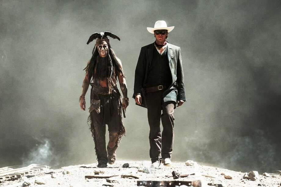 "Johnny Depp, left, as Tonto, and Armie Hammer as The Lone Ranger, are seen in a scene from the film ""The Lone Ranger."" Domestic box office numbers so far on this long Fourth of July holiday weekend are suggesting the highly anticipated, $250 million Western extravaganza is in serious danger of becoming the train wreck of the summer movie season. AP Photo/Disney/Jerry Bruckheimer, Inc., Peter Mountain, File"
