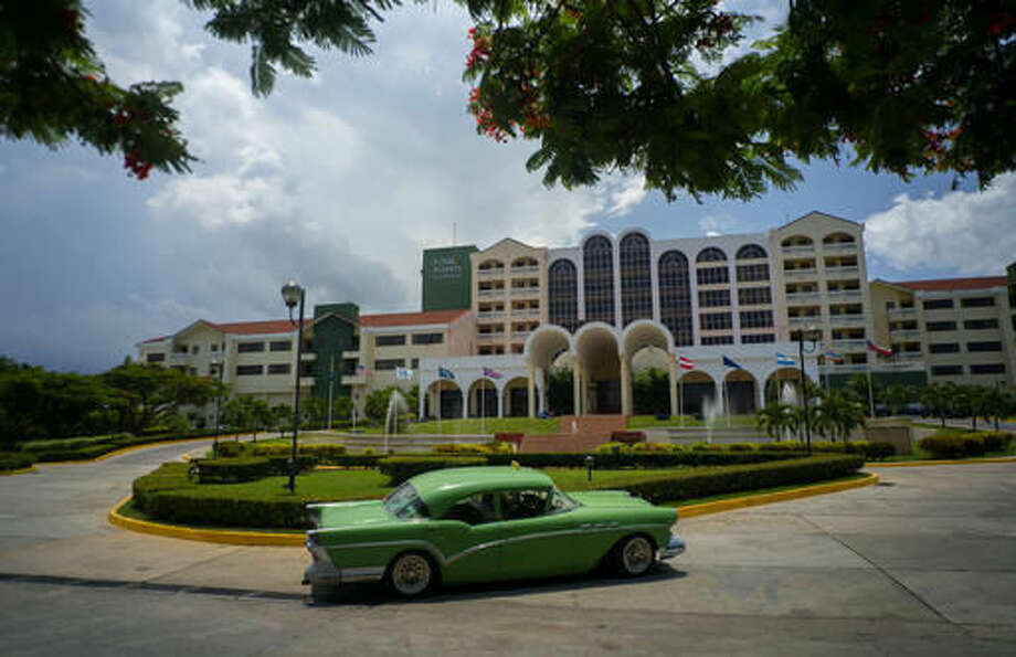 FILE - In this June 28, 2016 file photo, a vintage car passes in front of the Four Points by Sheraton hotel in Havana, Cuba. American hotel giant Starwood has begun managing this hotel owned by the Cuban military. Gaviota, the military's tourism arm, is in the midst of a hotel building spree that outpaces projects under control of nominally civilian agencies like the Ministry of Tourism. (AP Photo/Ramon Espinosa)