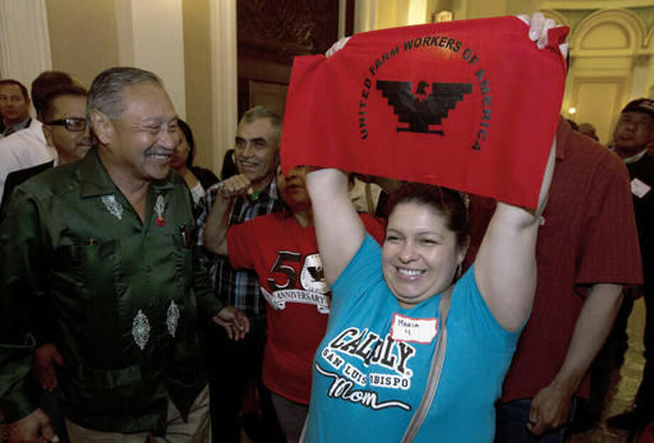 FILE -- In this Aug. 29, 2016 file photo Maria Ceja, right, joined other farm workers in celebrating outside the Assembly Chambers after lawmakers approved a measure requiring farmworkers to receive overtime pay after working eight hours, at the Capitol, in Sacramento, Calif. Calif. Gov. Jerry Brown, announced Monday, Sept. 12, 2016, that he signed the bill, AB1066, by Assemblywoman Lorena Gonzalez, D-San Diego. At left is Arturo Rodriguez, president of the United Farm Workers. (AP Photo/Rich Pedroncelli, File)