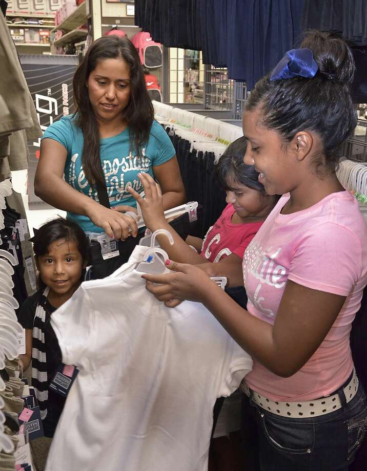 Paula Camacho shops for school uniforms for her daughters, Alexa, Jennifer and Stephanie, Wednesday morning at the Academy Sports and Outdoors on San Bernardo Avenue. A press conference was held at the store to announce that 900 United ISD students who attend Zaffirini Elementary would receive vouchers for their uniforms. Students were treated with CiCi's Pizza after the event. (Photo by Cuate Santos/Laredo Morning Times)