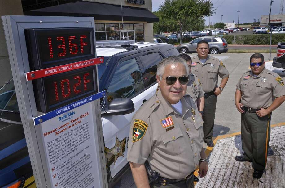 Sheriff Martin Cuellar and deputies Sergio Hernandez, Mario Reyes and Joe Cazares pose next to an electronic thermometer as it displays the difference between external and internal heat of a car Wednesday afternoon, outside of Quizno's. There have been 15 deaths related to children in overheated cars nationally this year, according to Child Protective Services spokesman John Lennan. CPS and the county gathered Wednesday to remind the community about the risk of hyperthermia. (Danny Zaragoza/Laredo Morning Times)