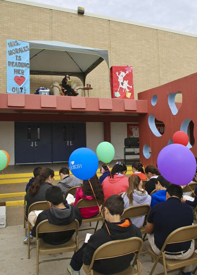 United Middle School principal Rebecca Morales reads to sixth grade students from the school's rooftop Thursday morning. The roof-top reading session was an incentive for students who accomplished reading 600 minutes during the month of October. (Photo by Victor Strife/Laredo Morning Times)