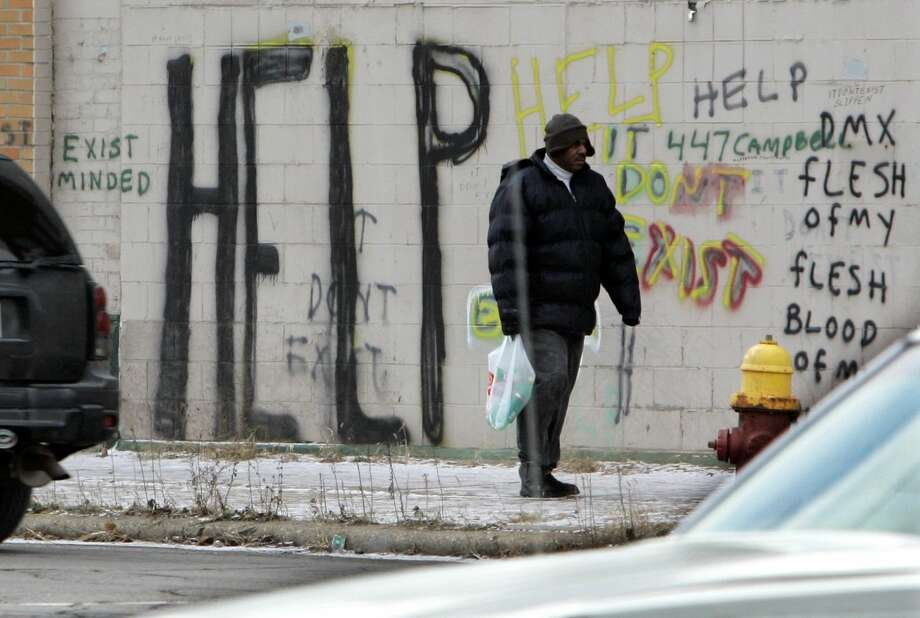 A pedestrian walks by graffiti in downtown Detroit in a Dec. 12, 2008, file photo. Detroit became the largest city in U.S. history to file for bankruptcy on Thursday, July 18, 2013, when state-appointed emergency manager Kevyn Orr asked a federal judge for municipal bankruptcy protection. (AP Photo/Carlos Osorio, File)
