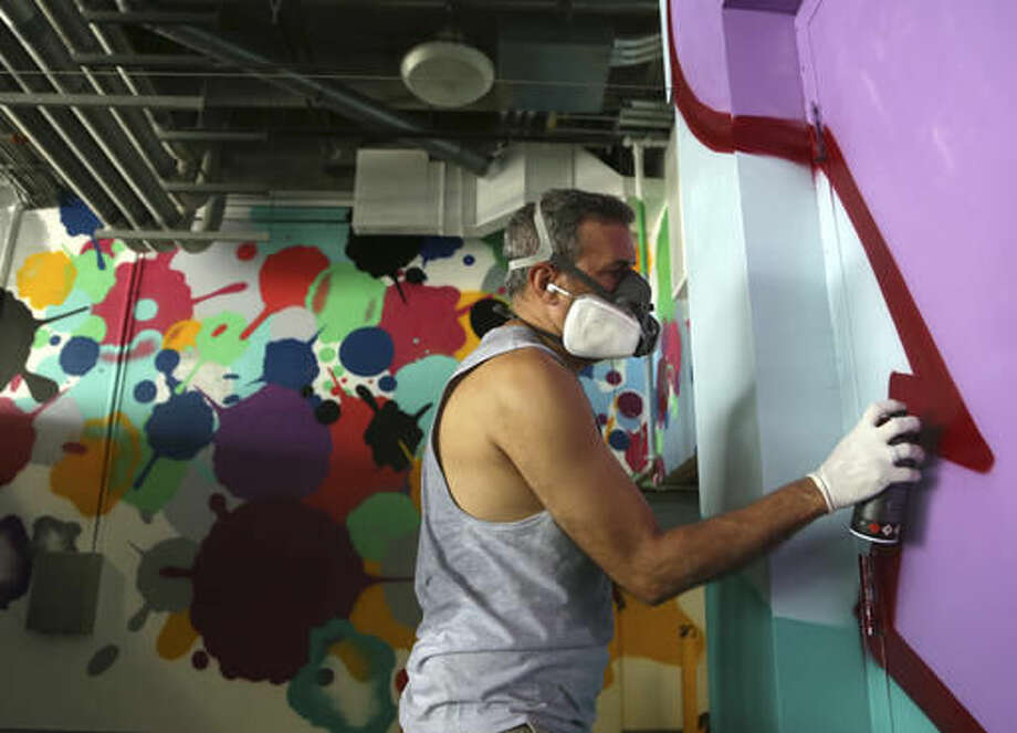 In this Tuesday, Sept. 20, 2016 photo, artist John Matos, known as CRASH, works on a mural at Hard Rock Stadium in Miami Gardens, Fla. When the Miami Dolphins play their home opener against the Cleveland Browns, it will be in a refurbished stadium that features 29,000 square feet of new, original wall art from artists from all over the world. (AP Photo/Lynne Sladky)