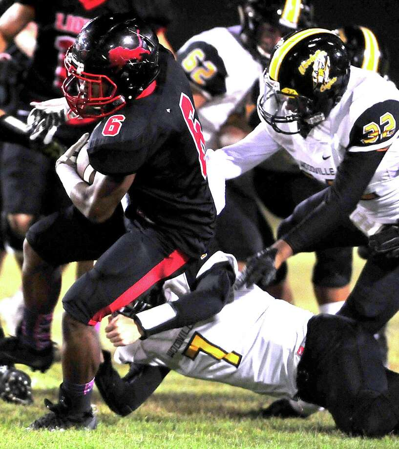 Kountze's Keyshawn Adams is tripped up by Woodville's Reed Weaver during Friday's game at Kountze. Photo taken Friday, October 21, 2016 Kim Brent/The Enterprise Photo: Kim Brent / Beaumont Enterprise