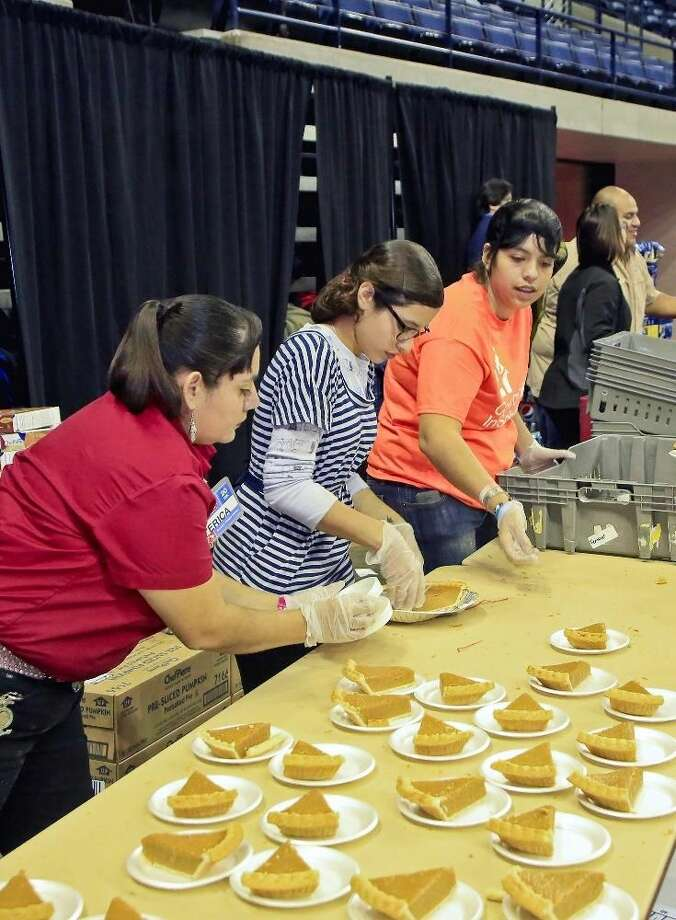 H-E-B employee Erica Rodriguez and student volunteers Sue Rivera and Paola Sepulveda prepare servings of pumpkin pie for the 25th Annual H-E-B Feast of Sharing at the Laredo Energy Arena on Sunday.