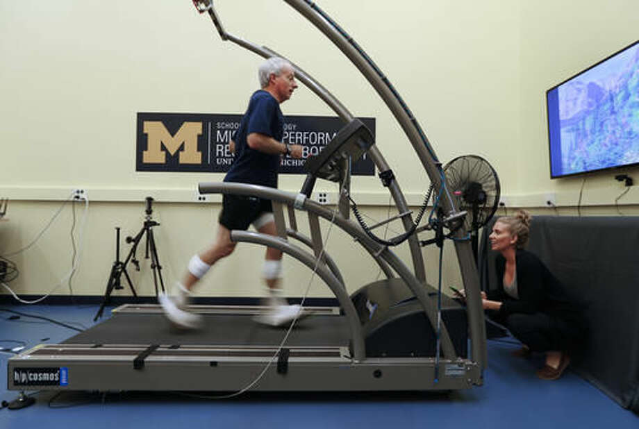 In this Friday, Aug. 12, 2016 photo, Cristine Agresta, right, watches David Moran run on a treadmill in Ann Arbor, Mich. A University of Michigan lab, The Michigan Performance Research Laboratory, which is part of the School of Kinesiology, is offering runners an in-depth assessment designed to help them improve their form. The consultations last around two hours and include footwear, musculoskeletal and postural evaluations by a physical therapist as well as footprint pressure and full-body 3-D gait analyses. (AP Photo/Paul Sancya)