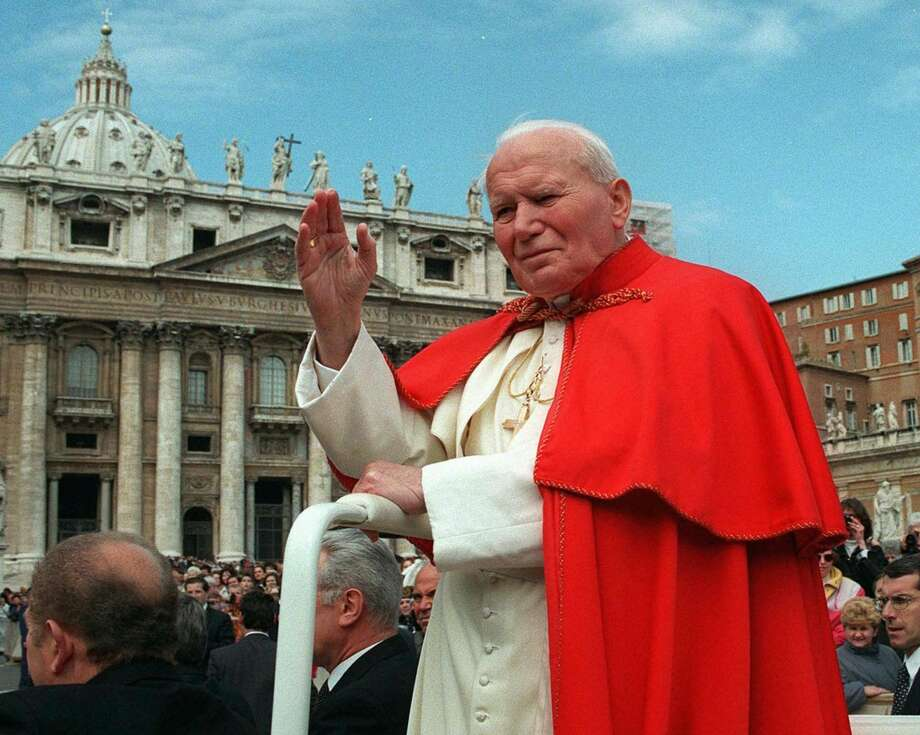 FILE - In this file photo taken on April 23 1997, Pope John Paul II waves to faithful as he crosses St. Peter's square at the Vatican. Pope Francis has cleared John Paul II for sainthood, approving a miracle attributed to his intercession. Francis also decided Friday, July 5, 2013, to canonize another beloved pope, John XXIII, even though there has been no second miracle attributed to his intercession. The Vatican said Francis approved a decision by cardinals and bishops. The ceremonies are expected before the end of the year. (AP Photo/Andrew Medichini/File)