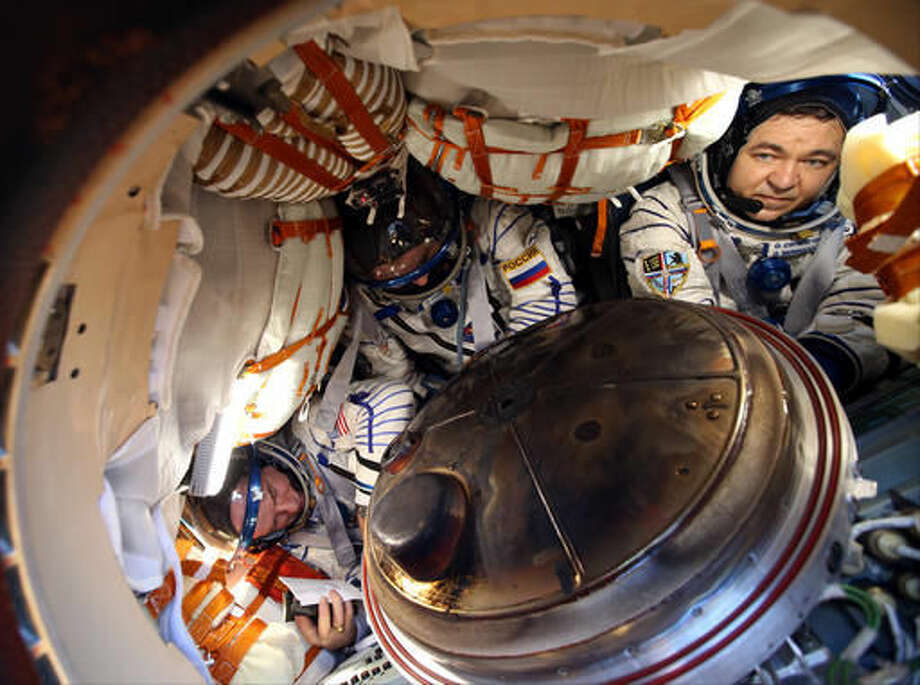 NASA astronaut Jeff Williams, left, Russian cosmonauts Alexey Ovchinin, center, and Oleg Skripochka of Roscosmos are seen inside the Soyuz TMA-20M spacecraft a few moments after they landed in a remote area near the town of Zhezkazgan, Kazakhstan, Wednesday, Sept. 7, 2016. The record-setting American and two Russians landed safely back on Earth Wednesday after a six-month mission aboard the International Space Station. (Maxim Shipenkov/Pool Photo via AP)