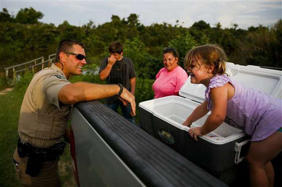 In an Aug. 26, 2016 photo,Texas Game Warden Dustin Dockery, left, laughs as Emma Reeves, 4, right, proudly shows off the perch in the cooler that her brother caught near Anahuac, Texas. For Dockery and the state's 550 game wardens, the job is anything but predictable as they patrol the vast open spaces of Texas. (Michael Ciaglo/ Houston Chronicle via AP)