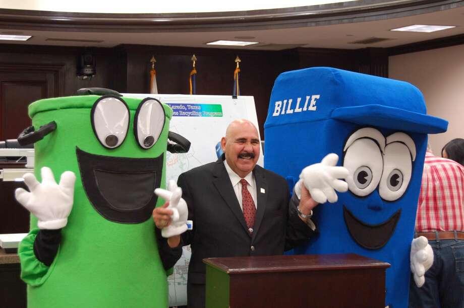 El Alcalde de la Ciudad de Laredo, Raúl G. Salinas, sonría mientras es rodeado por Willie Bote, en la presentación de su primo Billie Bote, el lunes. Billie Bote es la mascota para el programa de reciclaje que está previsto de inicio el 3 de octubre. (Foto de cortesía)