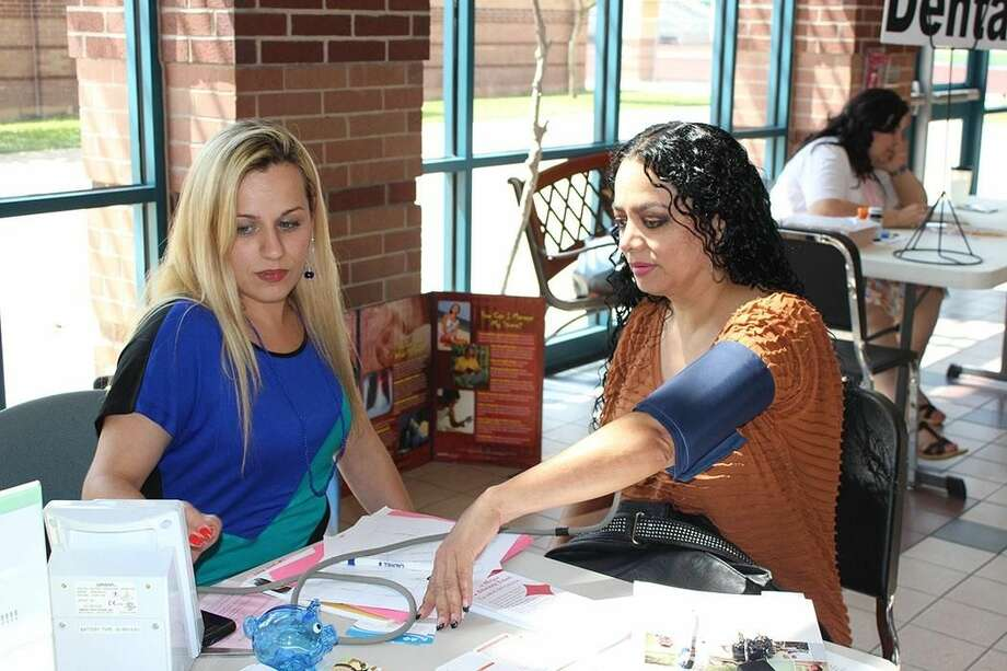 Arndt Elementary Teacher Aide Yolanda Pescador (pictured right) gets her blood pressure checked by Blue Cross Blue Shield Wellness Coordinator Michelle Silva, RN during an open enrollment session held recently at the Bill Johnson Student Activity Complex. Pescador was one of the many United Independent School District employees who attended the session. She took advantage of the free service that was offered at the event. Several other open enrollment sessions have been held throughout the District. (Courtesy photo)
