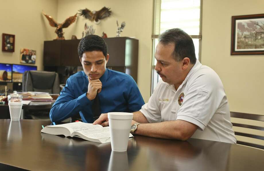 City of Laredo Fire Chief Steve E. Landin, left, shows Lyndon B. Johnson High School senior Ricardo Lara some of the fire station guidelines in the Texas Local Government Code Book at the Laredo Fire Department Thursday morning. Lara shadowed Landin throughout the morning shift and took on the position of fire chief as part of Youth Appreciation Day. (Photo by Victor Strife/Laredo Morning Times)