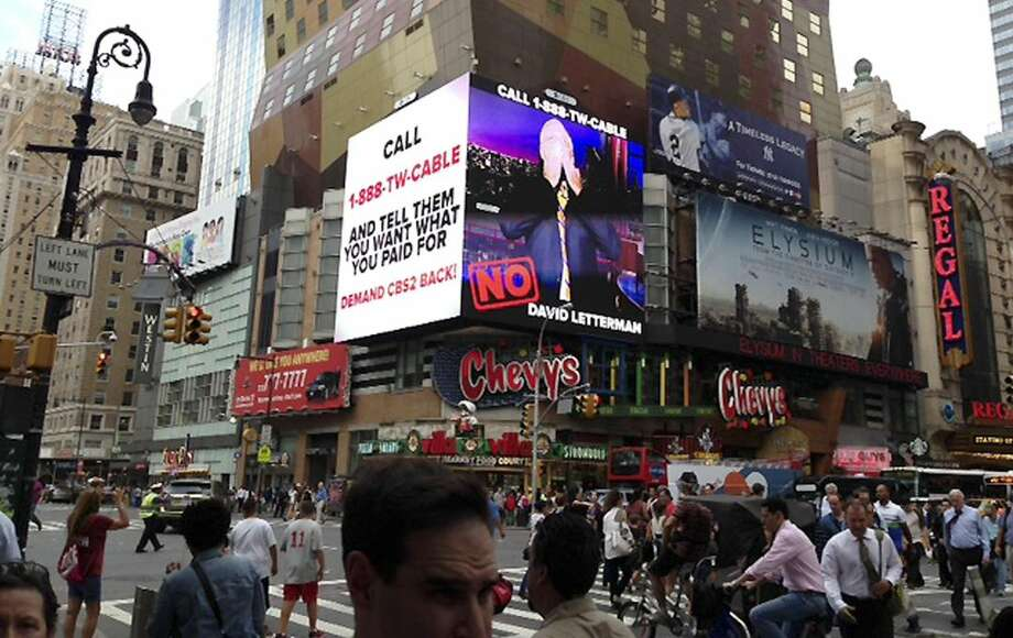 "This image provided by CBS shows a CBS advertisement in Times Square in New York on Friday, Aug. 2, 2013. Three million Time Warner Cable customers in New York, Los Angeles and Dallas lost access to CBS programming in a fee dispute Friday, threatening their ability to watch popular shows like ""Under the Dome"" or see Tiger Woods pursue his 8th win at the Bridgestone Invitational. The nation's second largest cable operator said that CBS refused to have productive negotiations, which were repeatedly extended after their previous deal expired at the end of June. (AP Photo/CBS)"
