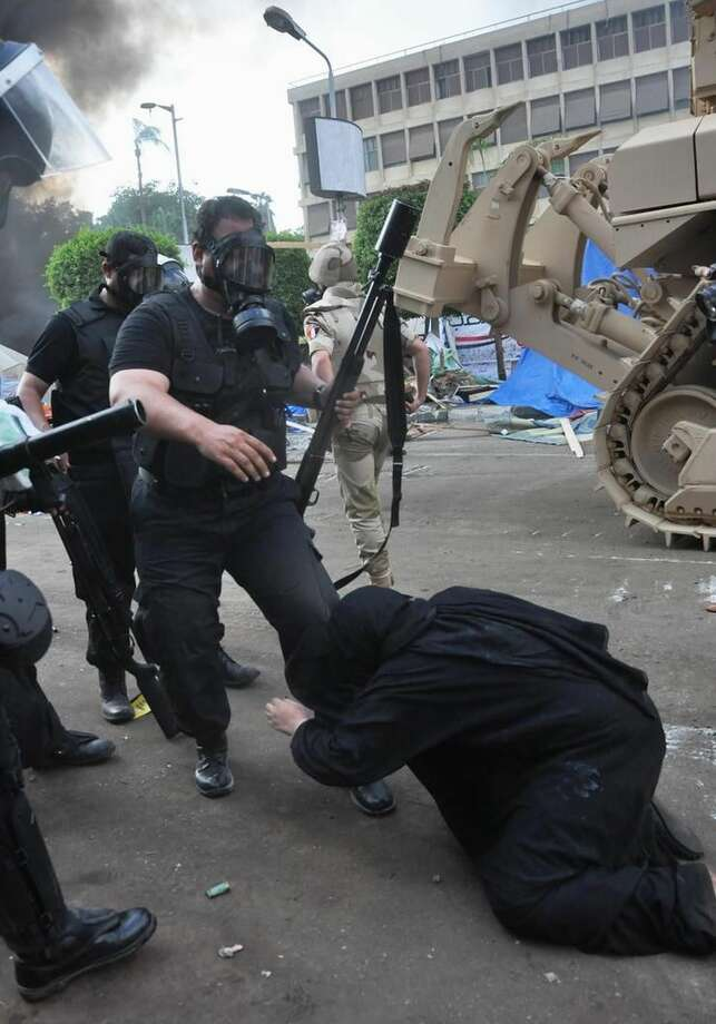Egypt in crisisAn Egyptian security force confronts a woman at a sit-in camp set up by supporters of ousted Islamist President Mohammed Morsi near Cairo University in Cairo's Giza district, Egypt, Wednesday, Aug. 14, 2013. Egyptian police in riot gear swept in with armored vehicles and bulldozers Wednesday to clear the sit-in camp and the other encampment set up by supporters of the country's ousted Islamist president in Cairo, showering protesters with tear gas as the sound of gunfire rang out. (AP Photo/Hussein Tallal)