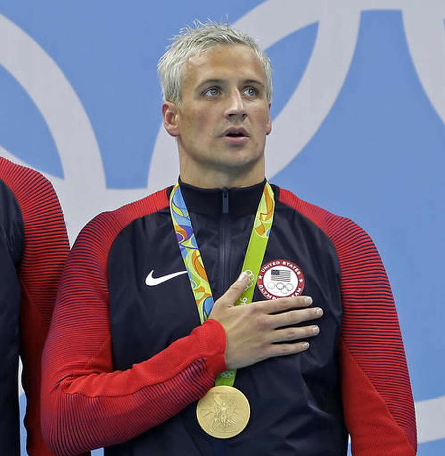 FILE - In this Aug. 10, 2016, file photo, Ryan Lochte listens to the national anthem after being awarded a gold medal during the ceremony for the men's 4x200-meter freestyle relay final at the 2016 Summer Olympics in Rio de Janeiro, Brazil. Lochte is banned from swimming through next June and will forfeit $100,000 in bonus money that went with his gold medal at the Olympics, part of the penalty for his drunken encounter at a gas station in Brazil during last month's games. The U.S. Olympic Committee and USA Swimming announced the penalties Thursday, Sept. 8, 2016. (AP Photo/Michael Sohn, File)