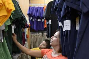 Reyna Badillo, foreground, and Francisco Colunga shop for school uniforms at Academy Sports and Outdoors on San Bernardo Avenue Friday morning. Shoppers are flocking to stores to take advantage of Texas' tax-free weekend for clothing and other items. (Photo by Cuate Santos/Laredo Morning Times)