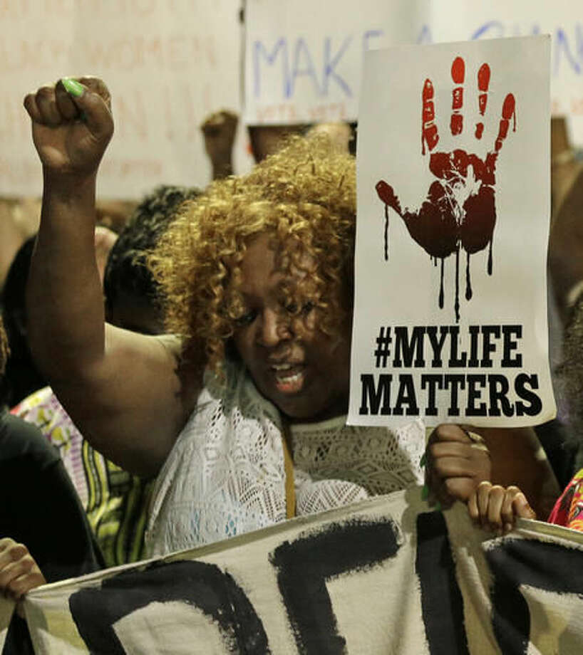 A protester raises her fist as she marches in the streets of Charlotte, N.C., Friday, Sept. 23, 2016, over Tuesday's fatal police shooting of Keith Lamont Scott. (AP Photo/Chuck Burton)