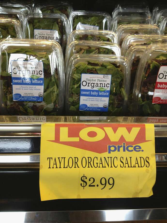 Packages of Taylor Farms salads are offered for sale at a supermarket in Omaha, Neb., Saturday, Aug. 3, 2013. (AP Photo/Nati Harnik)