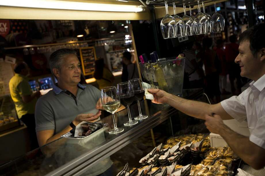 A man pays for drinks at a market bar in Madrid, Spain, on Tuesday, Aug. 13, 2013. After six quarters of a debilitating recession that has seen unemployment surge to record highs and public services being cut, the eurozone seems on the cusp of recovery. Official figures due to be released on upcoming Wednesday are widely expected to show that the economy of the 17 European Union countries that use the euro currency grew by a quarterly rate of 0.2 percent in the April to June period. (AP Photo/Daniel Ochoa de Olza)