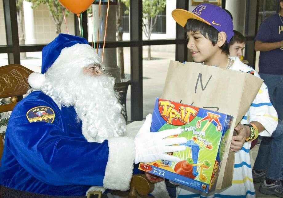 Adam Riley Bueno recibe un regalo durante la distribución de juguetes Blue Santa en las oficinas de la policía. (Foto de archivo/LMT)