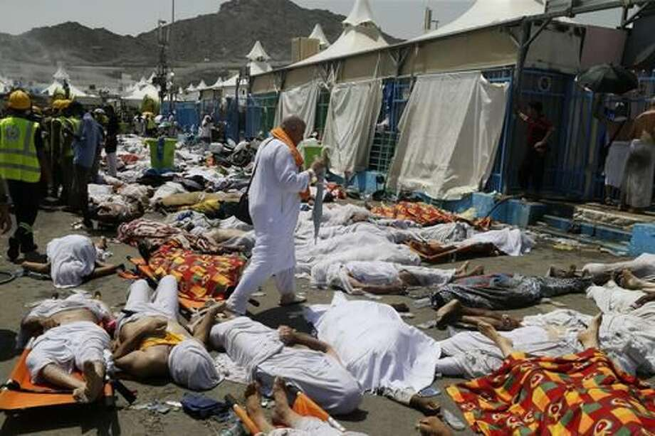 "FILE - In this Sept. 24, 2015, file photo, a Muslim pilgrim walks through the site where dead bodies are gathered after a stampede during the annual hajj pilgrimage, in Mina, Saudi Arabia. The website of Supreme Leader Ayatollah Ali Khamenei quotes him on Monday, Sept. 5, 2016, accusing Saudi Arabia of causing the death of injured pilgrims in last year's hajj stampede saying, ""The ruthless and criminal Saudi men locked half-alive injured people up along with the dead in tightly closed containers and martyred them."" (AP Photo, File)"