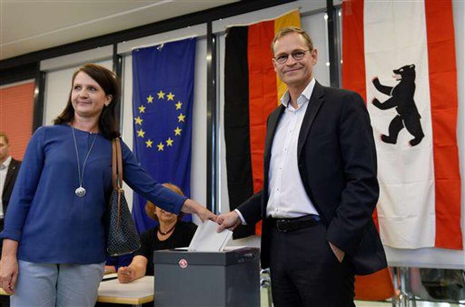Top candidate for the Social Democrats and governing Mayor of Berlin Michael Mueller, right, and his wife Claudia cast their votes in a polling station for the German federal state Berlin elections in Berlin, Sunday, Sept. 18, 2016. Voters in Berlin are casting ballots in a state election predicted to result in a fresh setback for Chancellor Angela Merkel's party. (Rainer Jensen/dpa via AP)
