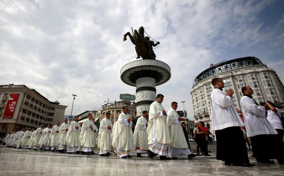 Catholic priests walk in a procession through the main square in Skopje, Macedonia, Sunday, Sept 11, 2016. Hundreds of people gathered Sunday at the main square in Macedonian capital Skopje for a ceremony of gratitude dedicated to Mother Teresa who Pope Francis has declared a saint last week in Vatican. (AP Photo/Boris Grdanoski)