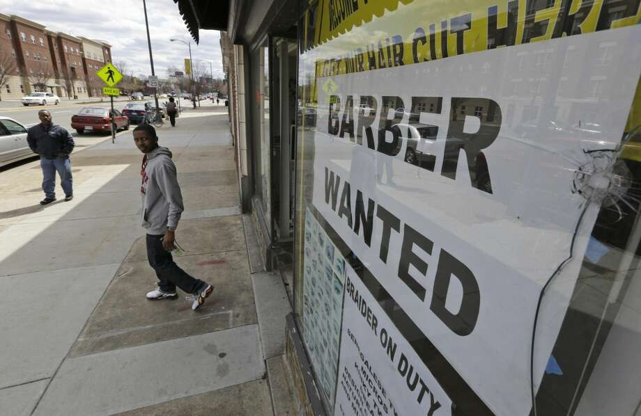 This Friday, March 29, 2013 photo shows a help wanted sign at a barber shop in Richmond, Va. U.S. employers added just 88,000 jobs in March, the fewest in nine months and a sharp retreat after a period of strong hiring. The slowdown is a reminder that the job market's path back to health will be uneven. (AP Photo/Steve Helber)