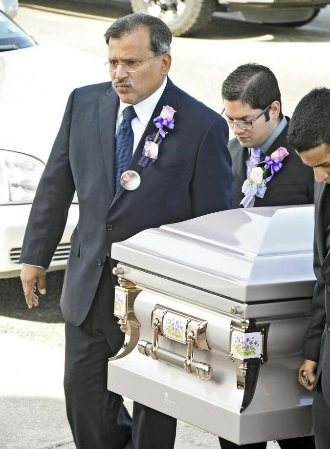 Police veteran Abraham H. Diaz Jr. carries the casket holding his daughter, Lilivette, as he walks into Holy Redeemer Church on Friday morning. Lilivette Diaz died in a two-vehicle collision early Sunday morning. (Photo by Ulysses S. Romero/Laredo Morning Times)