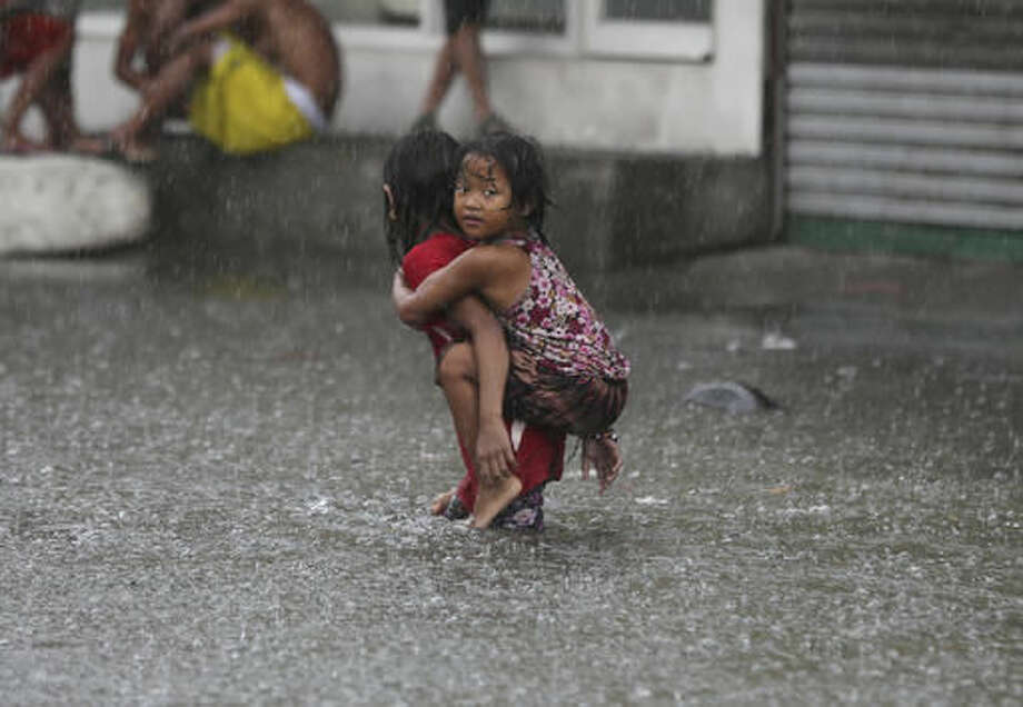 FILE In this July 8, 2016, file photo, a Filipino girl is carried along a flooded road in suburban Mandaluyong, east of Manila, Philippines, as monsoon downpours intensify while Typhoon Nepartak exits the country. This past summer's weather was relentless and hellish, crowded with the type of record-smashing extremes that scientists have long warned about. The season ends Wednesday, Sept. 21, 2016, and not a moment too soon. Summer featured floods that killed hundreds of people and caused more than $50 billion in losses around the globe, from Louisiana and West Virginia to China, India, Europe and the Sudan. Meanwhile, droughts parched croplands and wildfires burned from California to Canada to China and India. Toss in unrelenting record heat. (AP Photo/Aaron Favila, File)