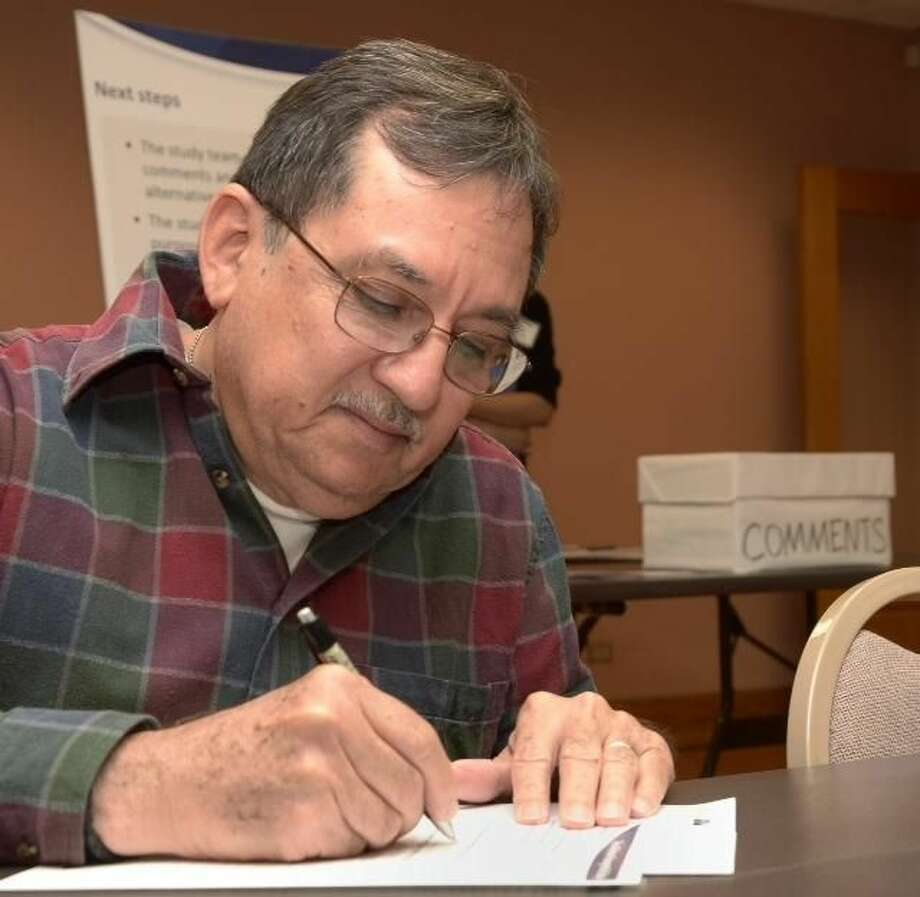 Laredoan Juan Medina writes his comments on the proposed passenger rail line at a town hall Wednesday evening at the TxDOT offices in Laredo. Officials from the city, Nuevo Laredo as far as Monterrey, Nuevo León, Mexico, contributed to the discussion.(Photo by Cuate Santos/Laredo Morning Times)