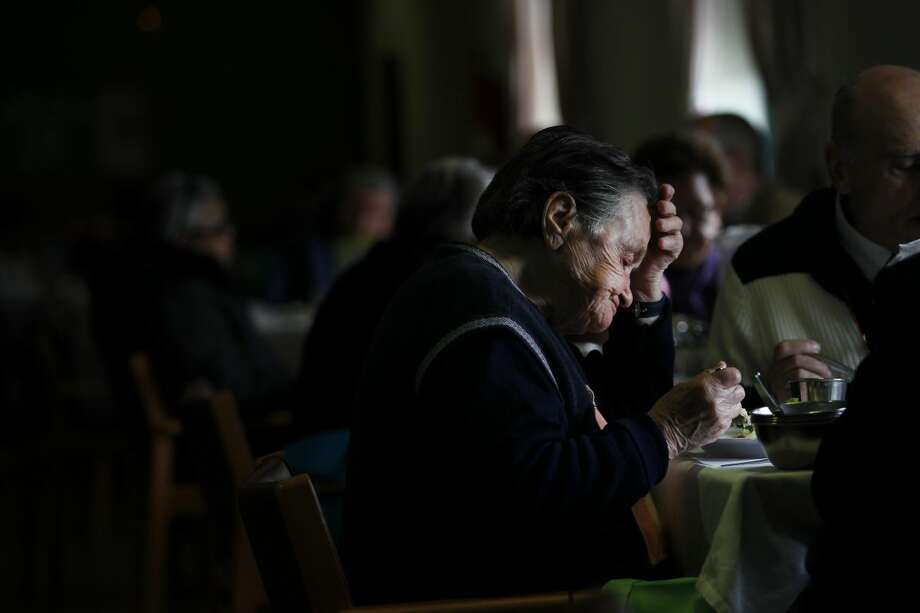 In this photo taken on February 20, 2013, an elderly woman eats her meal with other people in the eating hall of the Portuguese Catholic charity organization Santa Casa da Misericordia in Lisbon. Taxes and cuts in previous years had already cut pensioners income by 20 percent as the government looked to cut the national debt. (AP Photo/Francisco Seco)