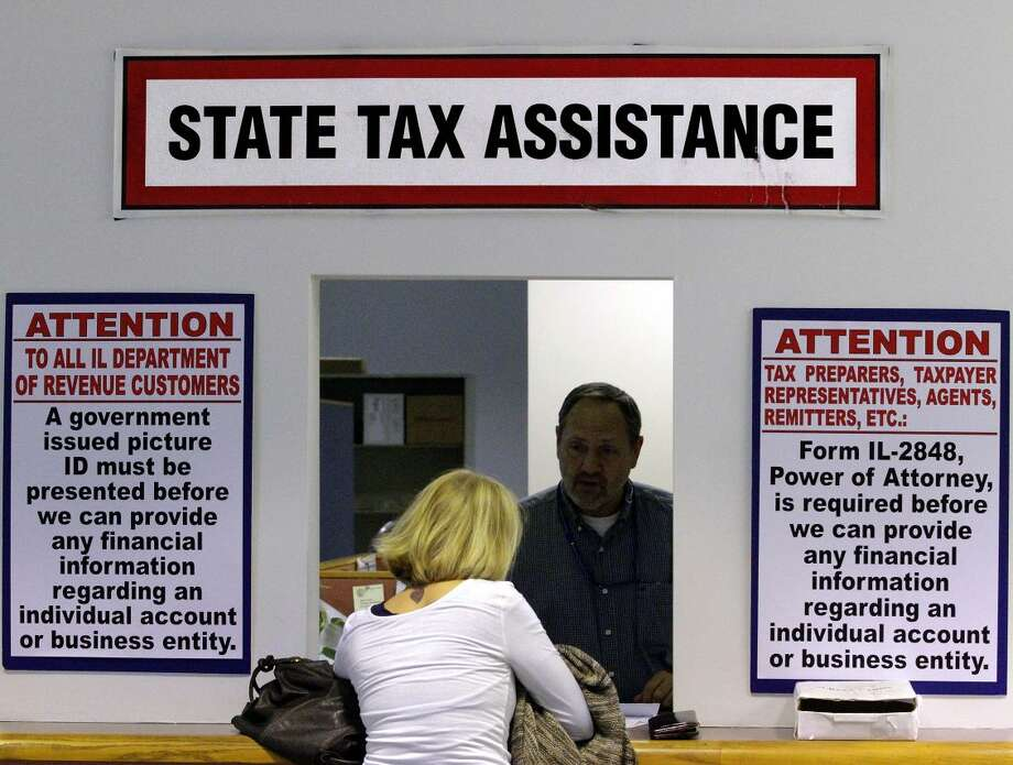 In this Monday, April 16, 2012 file photo, an Illinois Department of Revenue employee offers assistance to income tax payers at the Illinois Department of Revenue, in Springfield, Ill. Even with the advent of electronic filing, many Americans may not be able to deliver their tax return before the deadline Monday, April 15, 2013, at 11:59 p.m. EDT. However, the IRS will give you until Oct. 15 to file your return if you ask for an extension by midnight Tuesday, April 16. Last year, 10.7 million Americans did just that. (AP Photo/Seth Perlman, File)