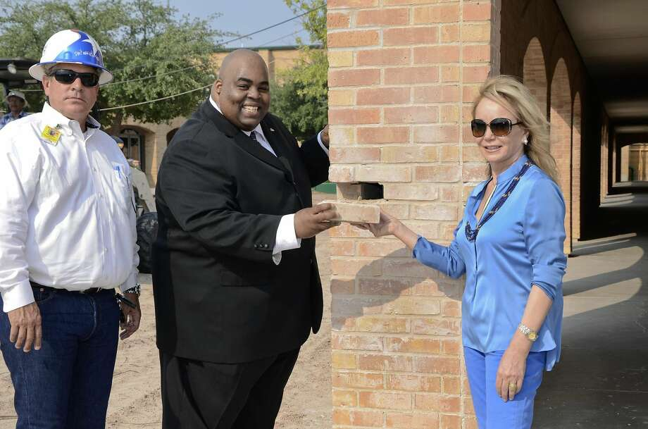 Mary Lamar Gallagher Leyendecker, a former student part of the 7th grade class who attended Nixon High School in 1964, is handed the first brick to be removed as part of the demolition process on the old campus by LISD Superintendent Marcus Nelson, second from left. When Nixon opened its doors in 1964, it was a junior/senior high school. The new $35 million replacement campus will be completed for the Fall 2015 semester. Leyendecker Construction Project Manager Greg Melendez, left, also attended the presentation. (Photo by Cuate Santos/Laredo Morning Times)
