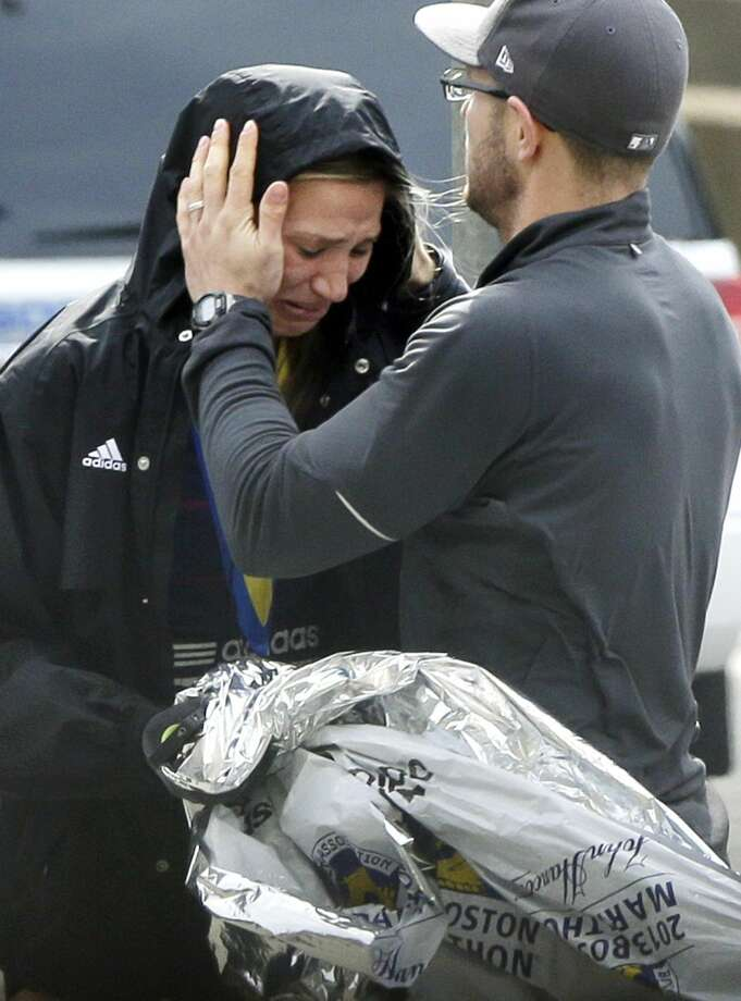 An unidentified Boston Marathon runner is comforted as she cries in the aftermath of two blasts which exploded near the finish line of the Boston Marathon in Boston, Monday, April 15. (AP Photo/Elise Amendola)
