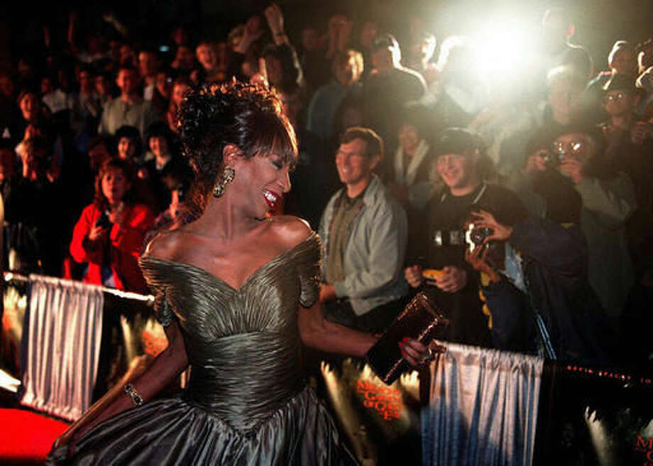 "In this Thursday, Nov. 20, 1997 file photo, The Lady Chablis twirls for the crowd awaiting the stars of the movie ""Midnight in the Garden of Good and Evil"" to arrive for the premier screening in Savannah, Ga. Chablis, the transgender performer who became a celebrity for her role in the 1994 best-seller ""Midnight in the Garden of Good and Evil,"" has died in Savannah. Chablis' sister, Cynthia Ponder, confirmed she died Thursday morning, Sept. 8, 2016, at a Savannah hospital. She was 59. (Scott Bryant/Savannah Morning News via AP)"